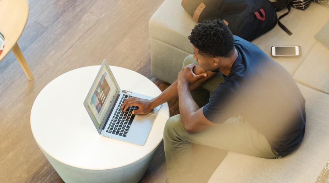 Person on MacBook logging onto LinkedIn