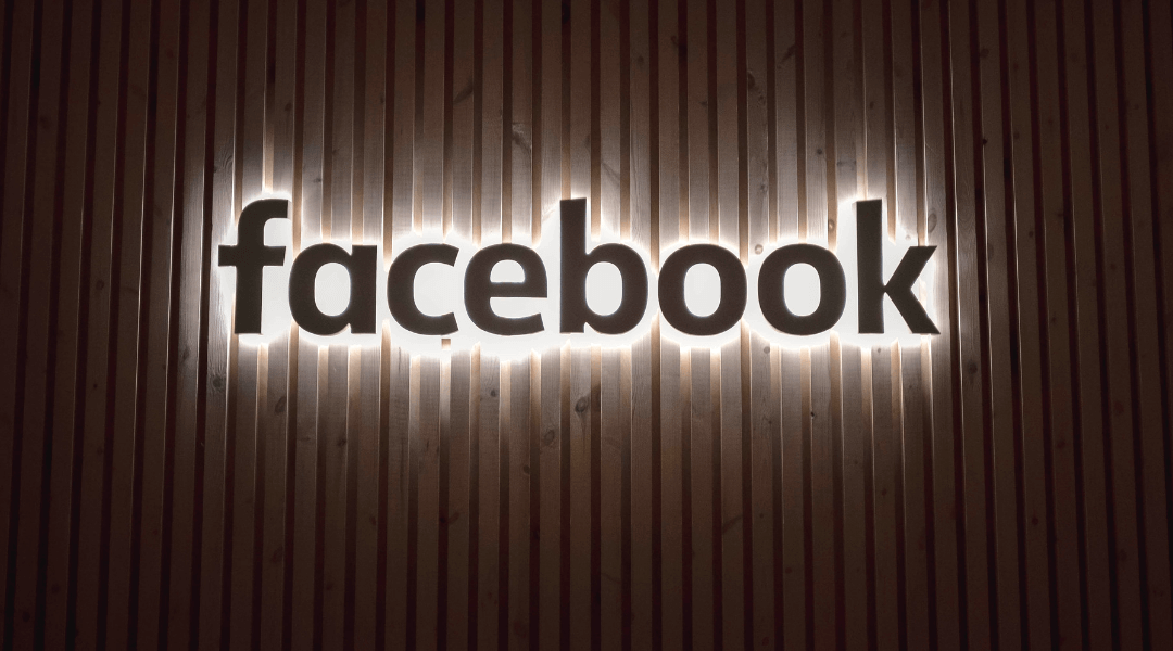 Illuminated Facebook logo on a brown wooden wall