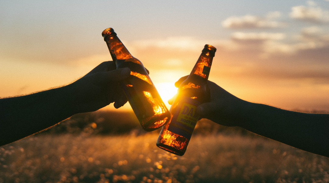 Two people cheersing with beers during a sunset