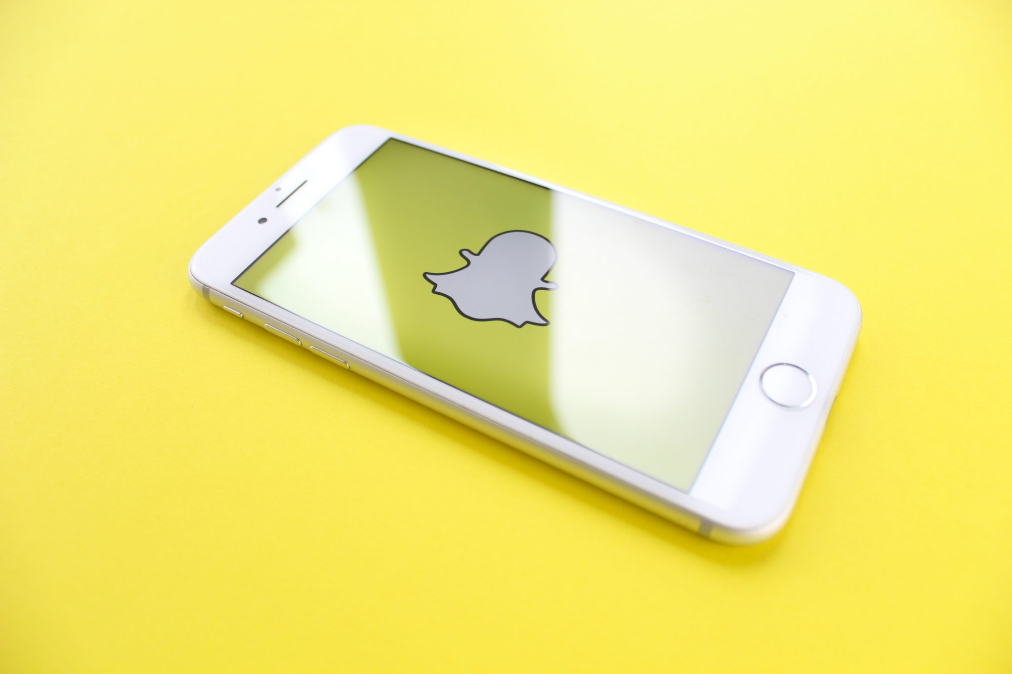 Snapchat ghost icon on iPhone 7 with a yellow background